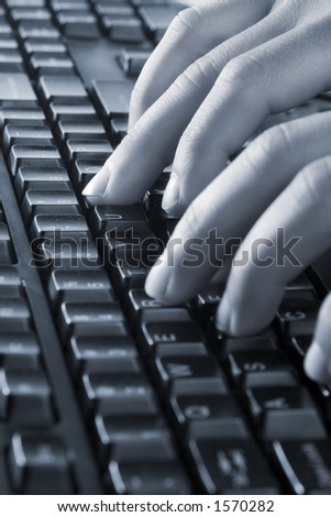 Hands on keyboard, blue color overall - stock photo