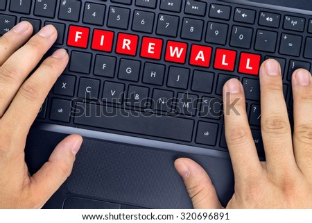"Hands on laptop with ""FIREWALL"" word on keyboard buttons."