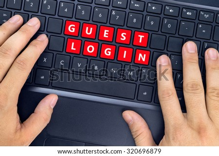 """Hands on laptop with """"GUEST LOGIN"""" words on keyboard buttons. - stock photo"""