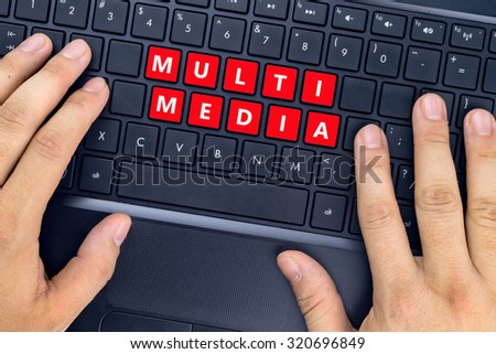 """Hands on laptop with """"MULTI MEDIA"""" words on keyboard buttons. - stock photo"""