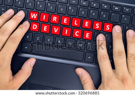 "Hands on laptop with ""WIRELESS DEVICE"" words on keyboard buttons. - stock photo"
