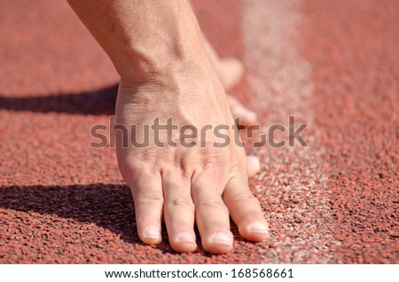 Hands on start line, wait to run. - stock photo