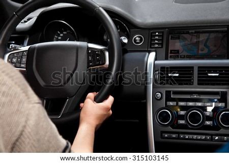 Hands on steering wheel in car interior