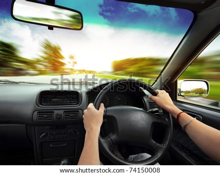 Hands on steering wheel of a car and blurred asphalt road - stock photo
