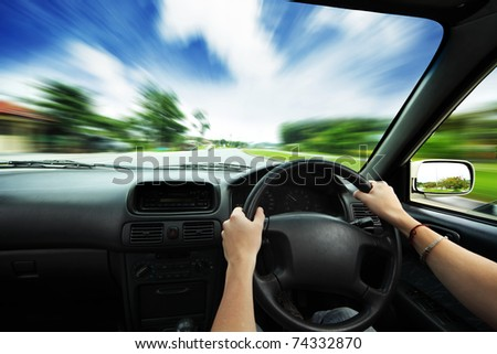Hands on steering wheel of a car and motion blurred asphalt road and sky - stock photo