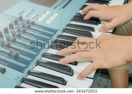 hands on the electric keyboard of the piano - stock photo