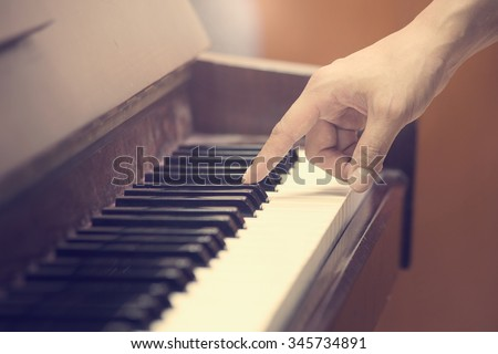 hands on the key of the piano,vintage tone  - stock photo