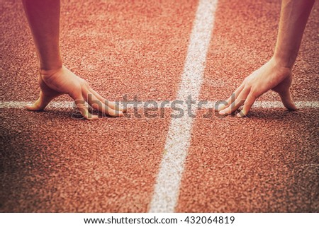 Hands on the starting line of a track and field running race - stock photo