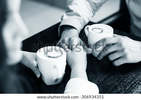 Hands on the table  holding cups of coffee - stock photo