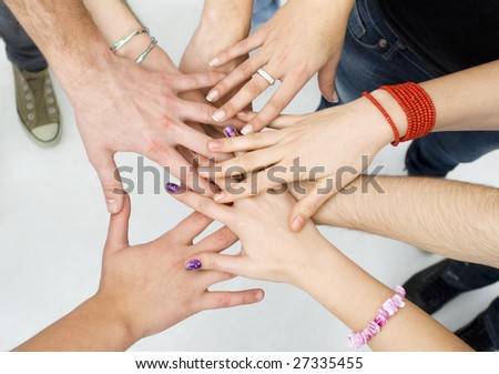 hands on top of each other; friendship concept - stock photo