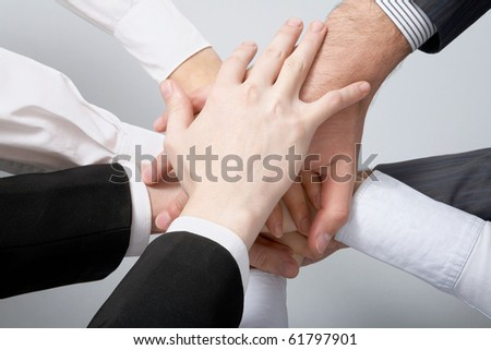 Hands on top of each other. Symbolic picture. - stock photo