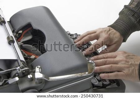 Hands on typewriter/Antique Typist/Man using a vintage typewriter - stock photo