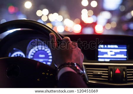 hands on wheel and city nightlife - stock photo