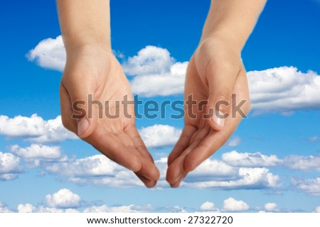 Hands open in religious prayer against sky background - stock photo