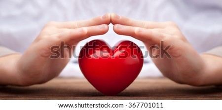 hands over a heart as safety concept - stock photo
