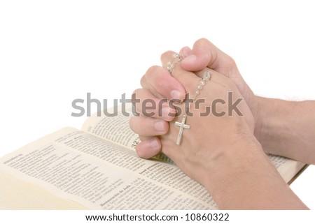 Hands over Bible praying - stock photo