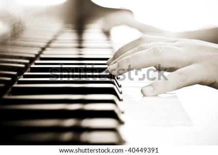 Hands over piano in beautiful sepia tone. - stock photo