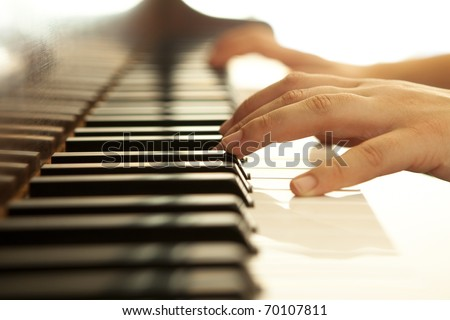Hands over piano in warm tones. - stock photo