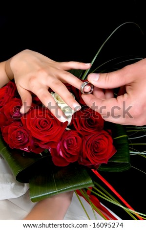 Hands over wedding bouquet with rings on black background, studio shot - stock photo