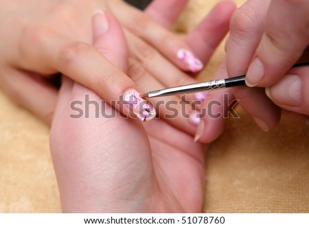 hands painting fingernails with a brush - stock photo