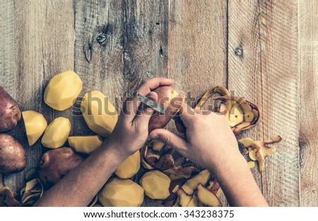 hands peeling potato on wooden board - stock photo