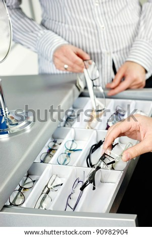 Hands picking up frames and glasses in optic shop - stock photo