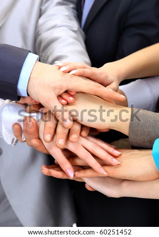 Hands piled on top of one another. - stock photo
