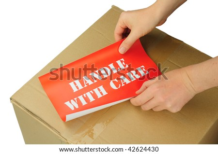 hands placing handle with care label on cardboard box - stock photo