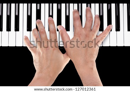 Hands playing a chord of Ab major over C bass on a piano keyboard shot from above with a black background. - stock photo