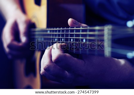 Hands playing acoustic guitar, close up - stock photo
