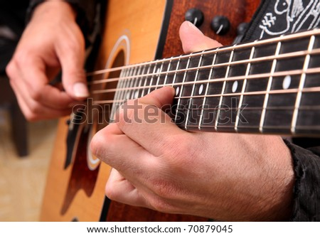 Hands playing guitar in diagonal position - stock photo