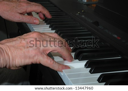 Hands playing music on a piano keyboard.