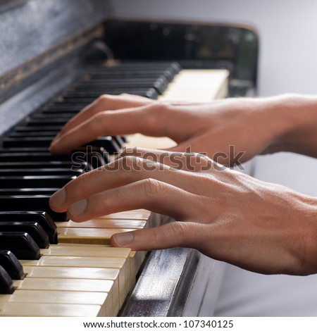 Hands Playing Old Piano - stock photo