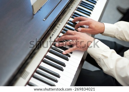 Hands playing the piano - stock photo