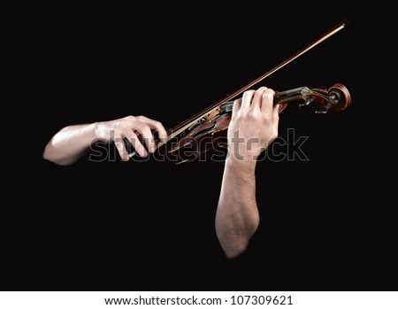 Hands playing  wooden violin on black background