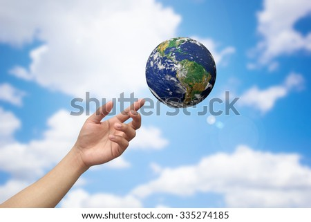 hands pointing/reaching the world on blur blue sky and clouds background wallpaper:man hand protection or helping concept:ecology and environment conceptual.Elements of this image furnished by NASA - stock photo