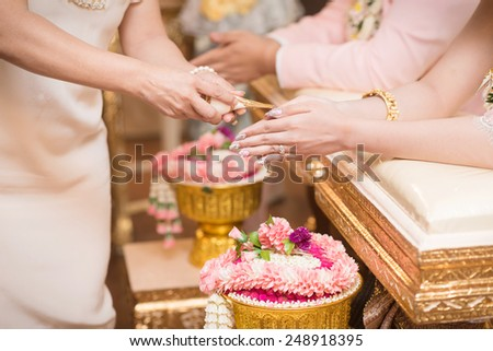 Hands pouring blessing water into bride's bands, Thai wedding. - stock photo