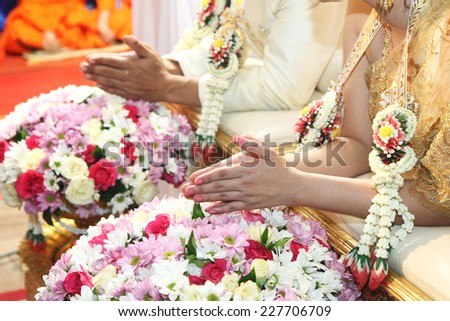 Hands pouring blessing water into bride's hands, Thai wedding ceremony. - stock photo