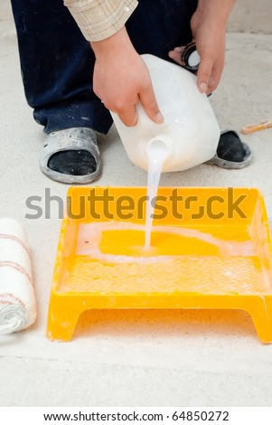 hands pouring paint from a large bucket - stock photo
