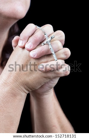 Hands praying and holding a small crucifix (isolated on black) - stock photo