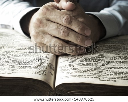 hands praying on bible - stock photo