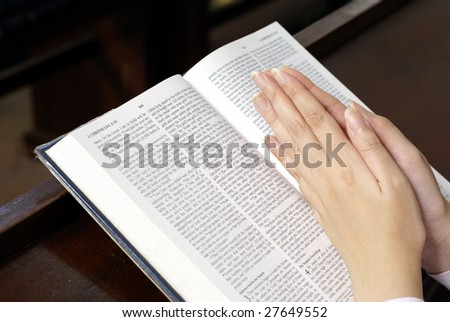 Hands praying on open bible