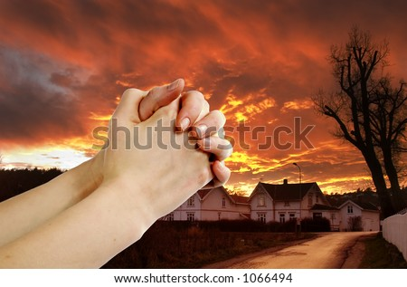 Hands praying with a dramatic red sky over a small town; prayer warrior. - stock photo