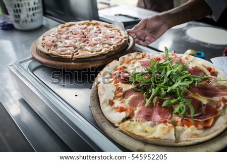 Hands preparing a pizza  (dark background)