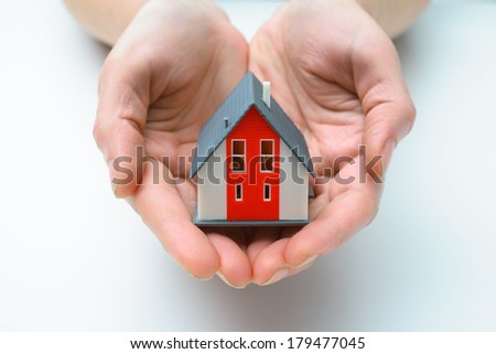 Hands presenting a small model of  house - stock photo