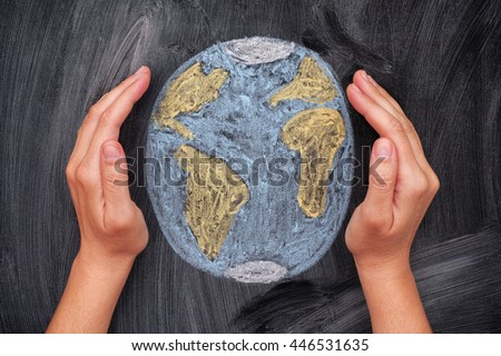 Hands protecting Planet Earth on black chalkboard background. Close up. - stock photo