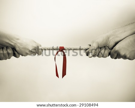 Hands pulling rope with red ribbon. Sepia tone. - stock photo