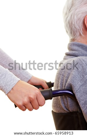 Hands pushing elderly person in a wheelchair