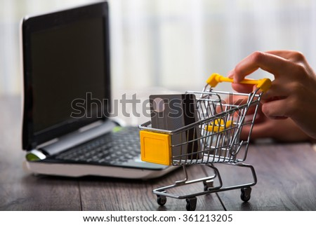 Hands pushing supermarket trolleys filled with credit card  - stock photo