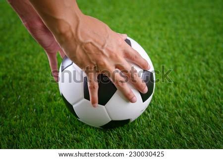 Hands put soccer ball on green turf - stock photo
